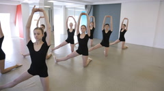 Girls stand in pose and do stretching exercise in dancing class Stock Footage