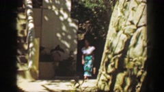 1952: Woman walking hotel resort tropical garden grounds in Mexican style dress. Stock Footage