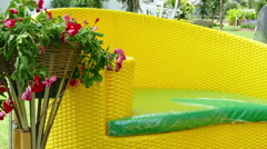 Yellow wicker style couch with green leather and red flower in flowerpot Stock Footage