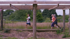 4K Competitors climbing monkey bars on assault course, 1 girl struggles Stock Footage