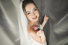 Beautiful young bride with makeup and hairstyle in bedroom, newlywed woman final Stock Photos