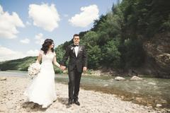 Elegant gentle stylish groom and bride near river with stones. Wedding couple in Stock Photos