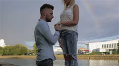 At the riverside man kissing a girl's hand and they walk away together Stock Footage