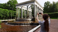 Woman make pictures of Lion Cascade at Peterhof Lower Gardens, slow motion Stock Footage