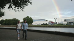 A happy couple walking under the rainbow in the park Stock Footage