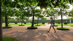 Young slim woman stroll in beautiful garden walkway, sun light flash Stock Footage