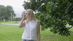 A blond young woman enjoying windy weather in a park Stock Footage