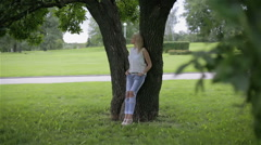 A girl leaning over a tree in a park Stock Footage