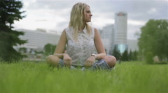 A girl sitting criss-crossed on a lawn Stock Footage