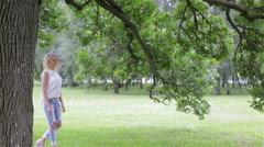 A fashionably dressed girl walking near a tree Stock Footage