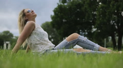 A young girl sitting on a grass. She puts off her sunglasses Stock Footage