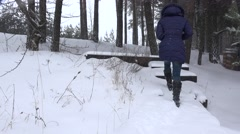 Woman climbs up stairs covered with snow in winter park. 4K Stock Footage