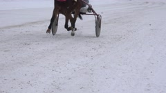 Race horse legs with riders in wheel carts compete on snowy track in winter. 4K Stock Footage