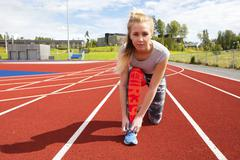 Athletic female runner tying shoelaces on running track Stock Photos