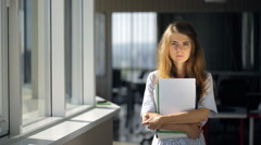 Young and beautiful female is standing in office corridor Stock Footage