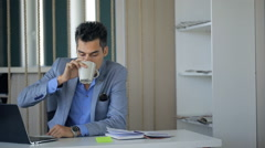 Business man is taking coffee break sitting at workplace continuing working Stock Footage