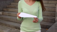 Girl hold in hands white paper plane, pinch if by fingers, ready to throw Stock Footage