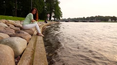 Woman sadly look to slow river waves, sit at stony bank, slow motion Stock Footage