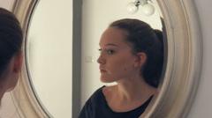 Beautiful young girl apply makeup at mirrow Stock Footage
