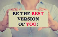 Businesswoman hands card sign with be the best version of you message - stock photo