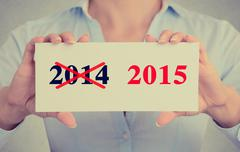 Businesswoman hands holding sign with year 2014 crossed and 2015 marked Stock Photos