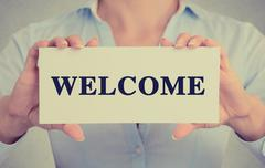 Closeup businesswoman hands holding card sign with welcome message Stock Photos