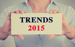 Businesswoman hands holding card sign with trends 2015 message - stock photo