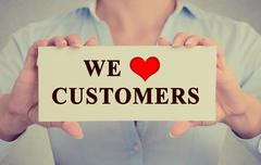 Image businesswoman hands holding sign with message we love customers Stock Photos