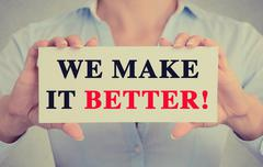 Businesswoman hands holding card with we make it better message Stock Photos