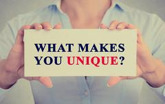 Businesswoman hands holding sign with message what Makes You Unique? Stock Photos