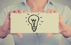 Closeup hands holding sign with hand drawn illuminated light bulb Stock Photos