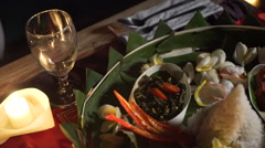 Plate with assorted indonesian food on palm leaf, evening with candles Stock Footage
