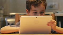 PORTRAIT: Cute little child holds at hands a white tablet PC at a table at home Stock Footage