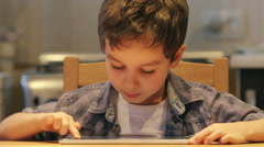 PORTRAIT: A cute little child uses a tablet PC at a table at home. Casual Stock Footage