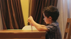 SIDE VIEW: Cute little child uses a tablet PC at a table at home Stock Footage