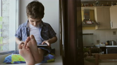 A cute little boy sits on a windowsill at home and touches a tablet PC Stock Footage