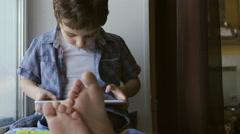 PORTRAIT: A cute little boy sits on a windowsill at home and touches a tablet PC Stock Footage