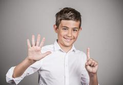 Handsome teenager showing 6 fingers, palm, number six gesture Stock Photos