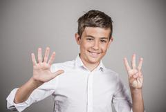Happy teenager showing eight fingers, number 8 gesture Stock Photos