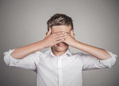Shy man closing covering eyes with hands. See no evil concept Stock Photos