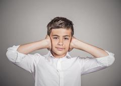 Boy covering ears with hands. Hear no evil Stock Photos
