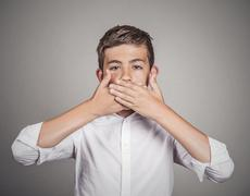 Student, boy, covering his mouth with hands. Speak no evil concept Stock Photos