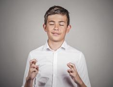 Man, teenager crossing fingers wishing, praying for miracle - stock photo