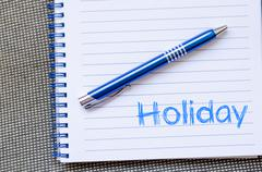 Holiday text concept on notebook Stock Photos