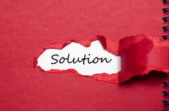 The word solution appearing behind torn paper Stock Photos
