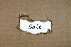 The word sale appearing behind torn paper Stock Photos