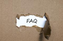 The word faq appearing behind torn paper Stock Photos