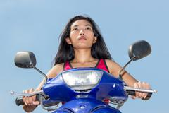 Woman sitting on a scooter on a blue background Kuvituskuvat