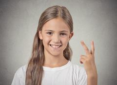 Happy teenager girl giving number two, victory sign Stock Photos