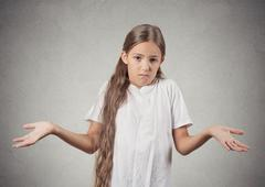 Clueless teenager girl shrugs shoulders Stock Photos